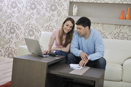 young couple at home with  modern livingroom indoor working on laptop on house finance and planing Stock Photo - 7840976