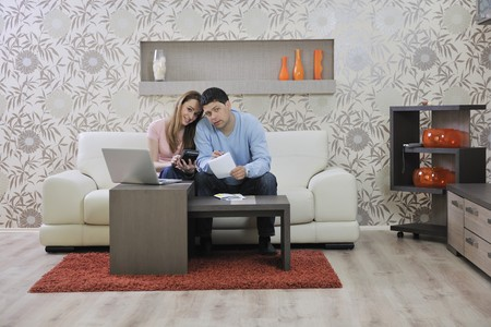 young couple at home with  modern livingroom indoor working on laptop on house finance and planing photo