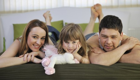 happy young family at home relaxing in bed  photo