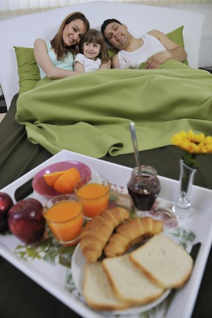 children breakfast: happy young family eat breakfast in bed at morning