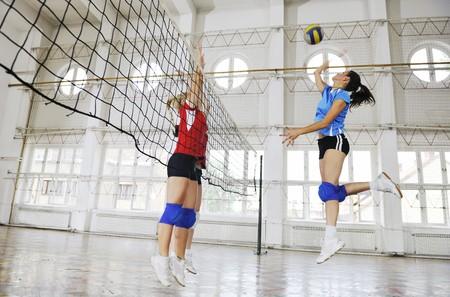 pelota de voley: deporte juego de voleibol con grupo de hermosas muchachas interiores en la arena de deporte