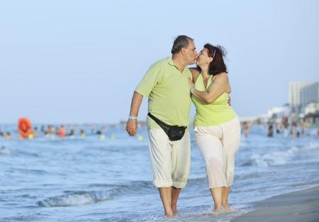 mujeres gordas: feliz pareja de personas de edad madura altos tiene tiempo rom�ntica en playa al atardecer