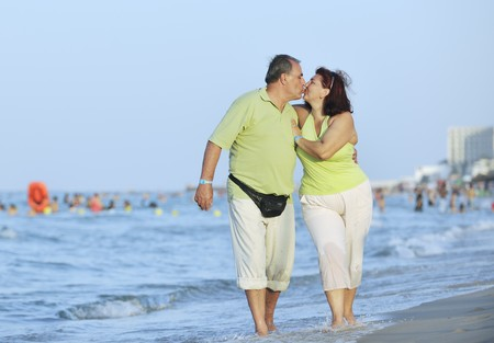 active couple: happy senior mature elderly people couple have romantic time on beach at sunset