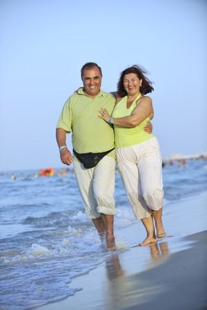 happy senior mature elderly people couple have romantic time on beach at sunset Stock Photo - 7615345