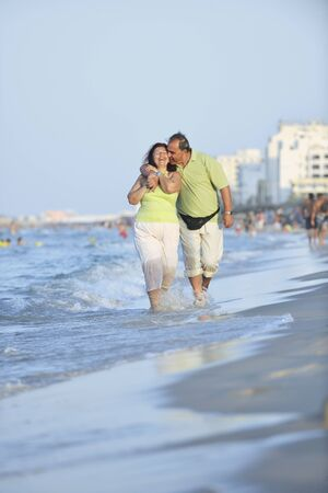 happy senior mature elderly people couple have romantic time on beach at sunset  photo