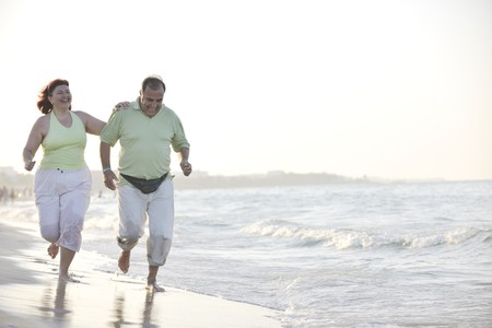 fat people: happy senior mature elderly people couple have romantic time on beach at sunset