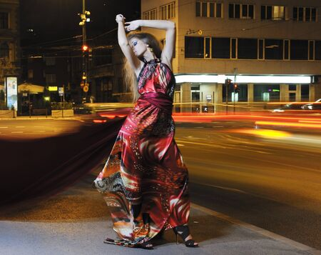 one beautiful young elegant woman in fashion and urban style dress in  city on  street at night alone photo
