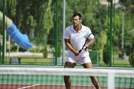 tenis: hombre joven jugar tenis al aire libre en la cancha de tenis naranja en temprano en la ma�ana