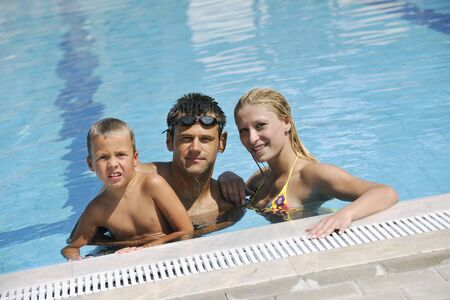happy young family have fun on swimming pool  at summer vacation Stock Photo - 7616692