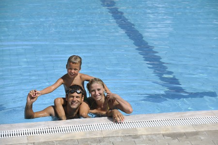 happy young family have fun on swimming pool  at summer vacation Stock Photo - 7616054