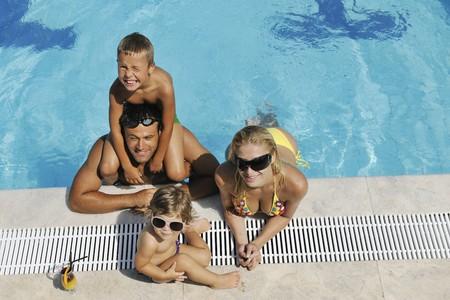 swim goggles: familia de joven feliz divertirse en la piscina en vacaciones de verano