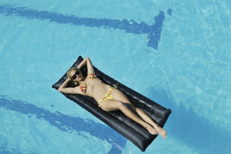 beautiful young woman enjoy sun and coctail dring relaxing and have fun at siwmming pool photo