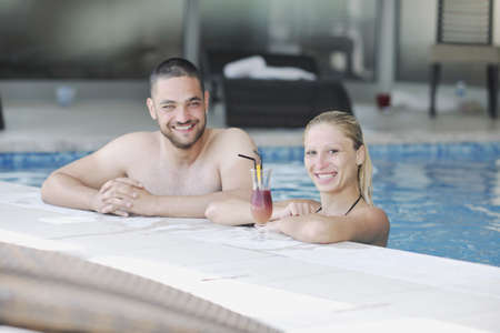 happy young couple in love have fun  relax and  drink coctail at indoor wellness swimming pool photo