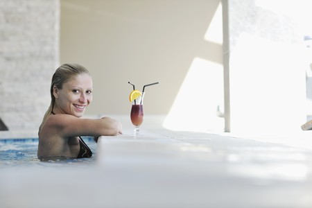 dring: beautiful young woman enjoy sun and coctail dring relaxing and have fun at siwmming pool
