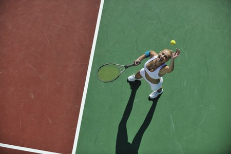 young fit woman play tennis outdoor on orange tennis field at early morning  photo
