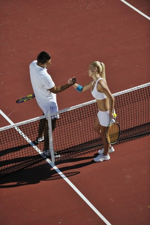 happy young couple play tennis game outdoor man and woman photo