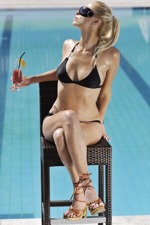 young beautiful woman relax drink coctail and have fun with splashing water at hotel swimming pool  photo