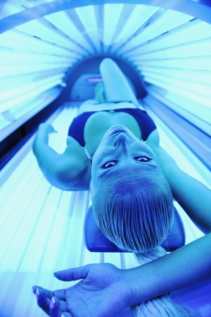 beauty salon face: young woman at laying on solarium bed and get brown skin tone ready for summer Stock Photo