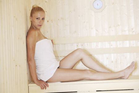 body temperature: beauty spa and wellnes body treatment with young woman at  wooden sauna