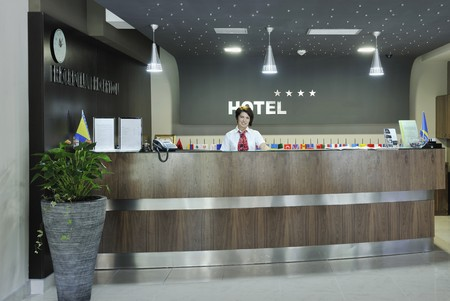 hotel reception: smiling businesswoman at the reception desk working
