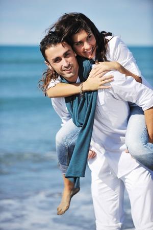 parejas jovenes: feliz pareja joven en prendas de vestir de blanco tiene esparcimiento rom�ntica y diversi�n en la hermosa playa de vacaciones