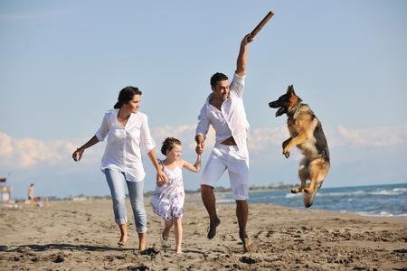 familia de joven feliz en el vestido blanco divertirse y jugar con hermoso perro en vacaciones en la playa