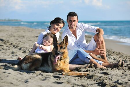 family holidays: happy young family in white clothing have fun and play with beautiful dog at vacations on beautiful beach  Stock Photo