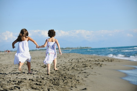happy two little girls have fun and joy time at beautiful beach while running from joy  Stock Photo