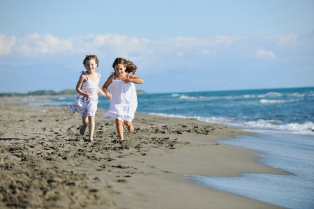 happy two little girls have fun and joy time at beautiful beach while running from joy Stock Photo - 8236442