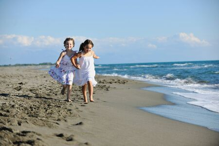 free running: happy two little girls have fun and joy time at beautiful beach while running from joy  Stock Photo