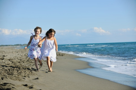 happy two little girls have fun and joy time at beautiful beach while running from joy Stock Photo - 8236480