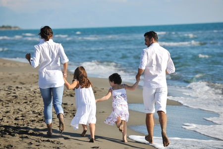 happy young family in white clothing have fun at vacations on beautiful beach Stock Photo - 8237213
