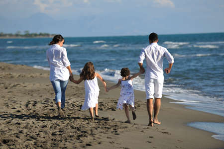 happy young family in white clothing have fun at vacations on beautiful beach Stock Photo - 8237168