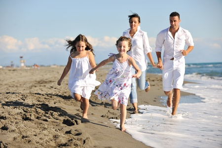 happy young family in white clothing have fun at vacations on beautiful beach  Stock Photo - 8236917