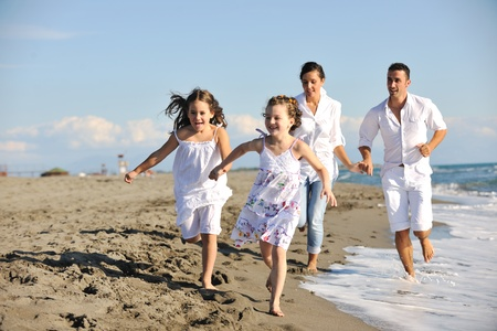 happy young family in white clothing have fun at vacations on beautiful beach  photo