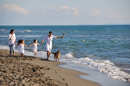 happy young family in white clothing have fun and play with beautiful dog at vacations on beautiful beach  Stock Photo - 8237683