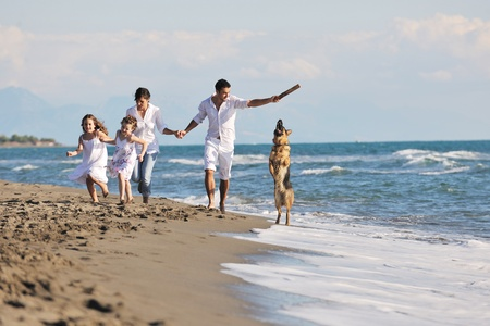 happy young family in white clothing have fun and play with beautiful dog at vacations on beautiful beach Stock Photo - 8236393
