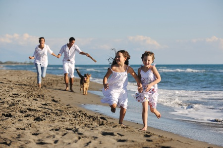 happy young family in white clothing have fun and play with beautiful dog at vacations on beautiful beach Stock Photo - 8236481