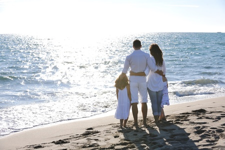 holidays family: happy young family in white clothing have fun at vacations on beautiful beach