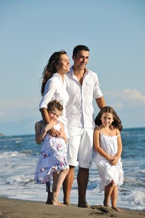 Happy young Family in weiße Kleidung haben Spaß an Ferien am schönen Strand
