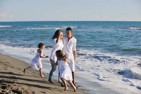 happy young family in white clothing have fun at vacations on beautiful beach Stock Photo - 8237557