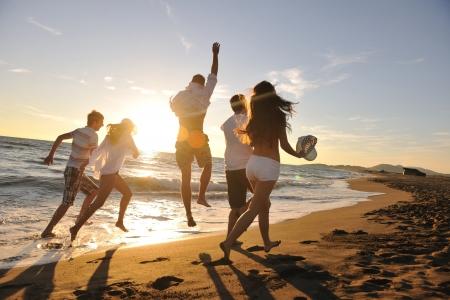 voyage: heureux groupe de jeunes gens ont la course blanche fun et en sautant sur beacz à l'heure du coucher du soleil
