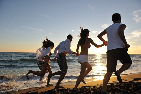 summer festival: happy young friends group have fun and celebrate while jumping and running on the beach at the sunset Stock Photo