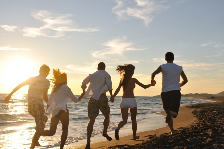 girl friends: happy young friends group have fun and celebrate while jumping and running on the beach at the sunset Stock Photo