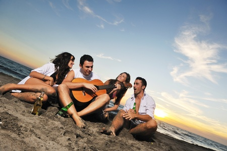 happy young friends group have fun and celebrate while jumping and running on the beach at the sunset Stock Photo - 8238974