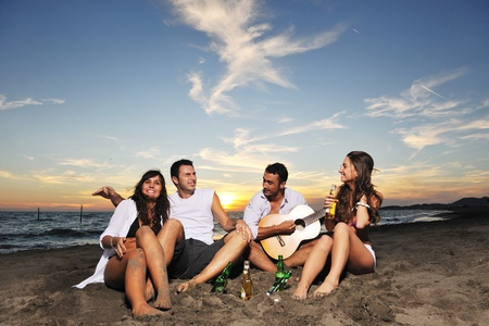 happy young friends group have fun and celebrate while jumping and running on the beach at the sunset Stock Photo - 8237740