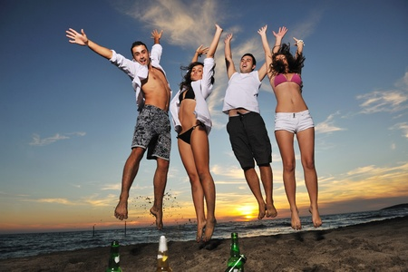 happy young friends group have fun and celebrate while jumping and running on the beach at the sunset Stock Photo - 8237817