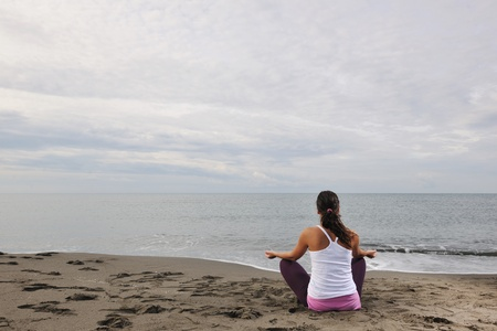 young woman meditating yoga in lotus positin on the beach at early morning photo