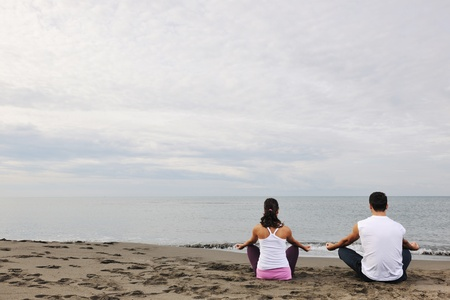 young couple people meditating yoga in lotus position at early morning on the beach Stock Photo - 8236456
