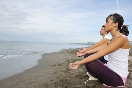 young couple people meditating yoga in lotus position at early morning on the beach photo